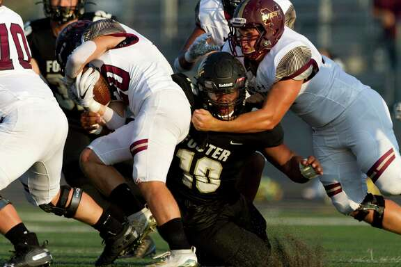 Foster nose guard Chidozie Nwankwo (10) wraps up Magnolia West running back Hunter Bilbo (20) during the first quarter of a non-district high school football game at Guy K. Traylor Stadium, Saturday, Sept. 14, 2019, in Rosenberg.