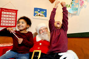 John Gordon, 3, of Glen Carbon, right, shouts for joy alongside his sister Elizabeth, 5, on Saturday during Santa at City Park in Edwardsville. Santa at City Park is in its eleventh year, and is presented by the Edwardsville Parks & Recreation Department. Visitors are welcome to visit Santa on Wednesdays from 5:30 to 8:30 p.m. and Saturdays from 1 to 4 p.m. until Dec. 21. Parents are encouraged to take photos while their children greet Santa Claus inside his decorated home at City Park, located at 101 S. Buchanan St. Families were able to see Santa arrive in a big red fire truck Saturday, courtesy of Edwardsville Fire Department.