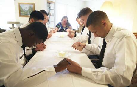 Pvt. Ryan Wooshalno, left, and Pvt. George Sanchez join with the group in offering a blessing as Jan and Travis Briggs hosts soldiers from Ft. Sam Houston at her home for Thanksgiving dinner on Nov. 28, 2019.