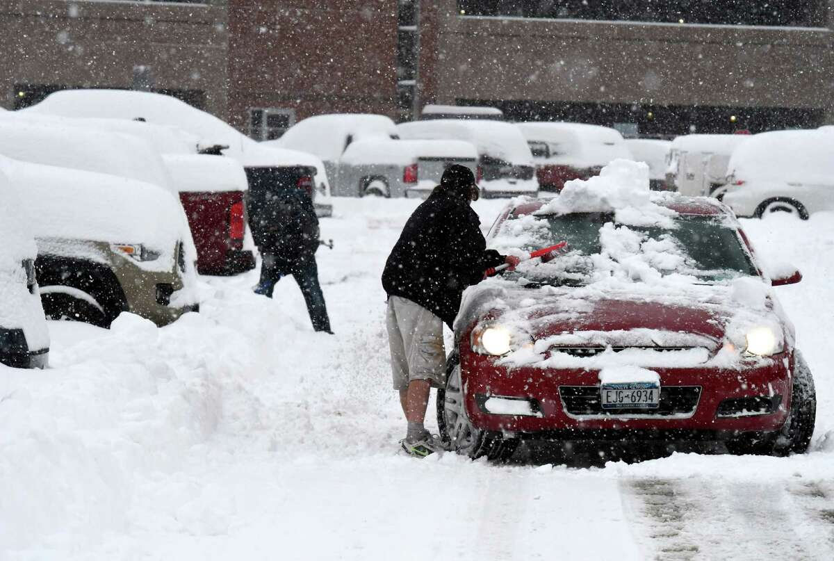 Brian McCaffrey of Delmar clears the snow from his car after returning from a trip to Disney World in Orlando, Florida on Monday, Dec. 2, 2019, at Albany International Airport in Colonie, N.Y. (Will Waldron/Times Union)