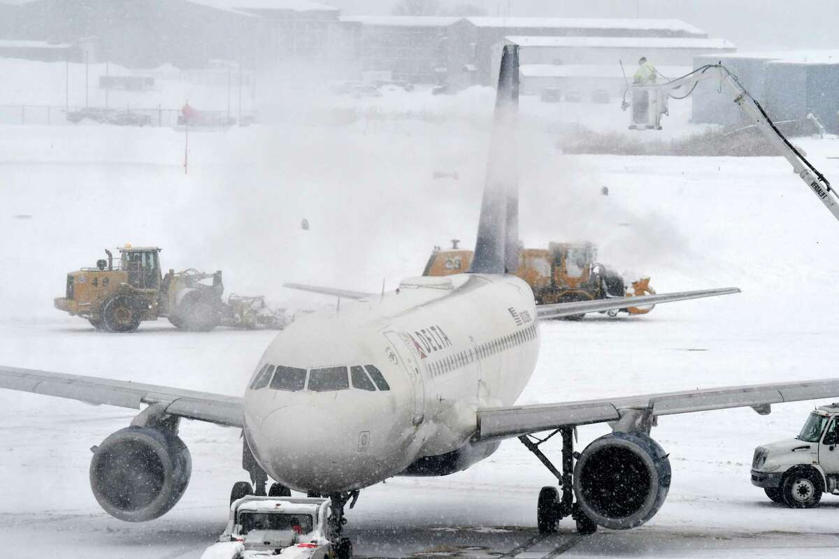Aircraft are deiced at Albany International Airport as a slow-moving snowstorm sweeps through the Capital Region on Monday, Dec. 2, 2019, in Colonie, N.Y. (Will Waldron/Times Union)