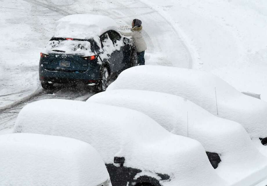 Travelers return to a snow-covered parking lot at Albany International Airport  on Monday, Dec. 2, 2019, in Colonie, N.Y. (Will Waldron/Times Union) Photo: Will Waldron, Albany Times Union / 40048373A