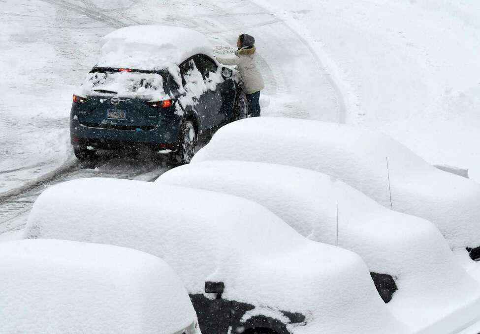 Travelers return to a snow-covered parking lot at Albany International Airport on Monday, Dec. 2, 2019, in Colonie, N.Y. (Will Waldron/Times Union)