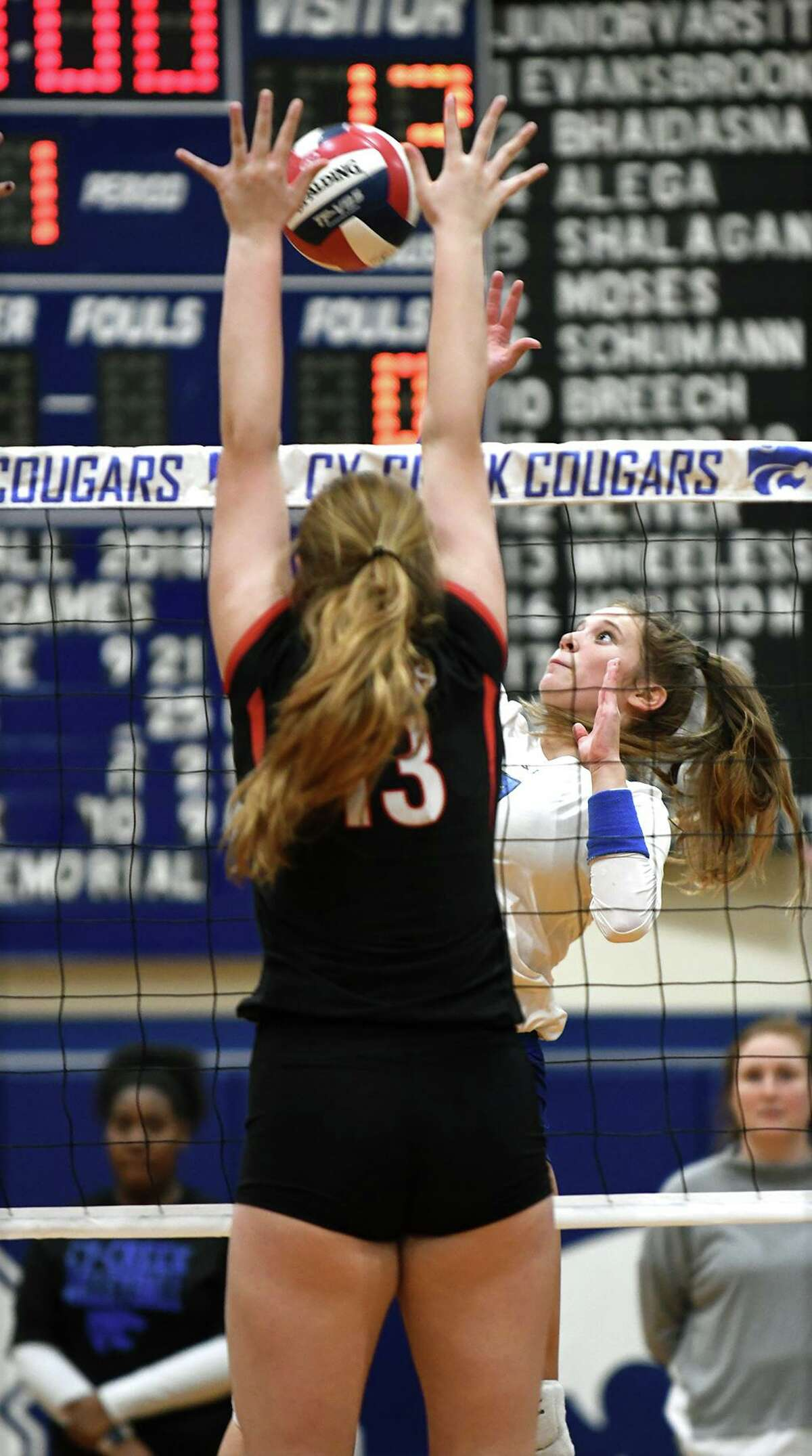Cy Creek junior outside hitter Alex Evans-Brooks, right, battles at the net against Memorial sophomore right side Logan LeRoux (13) during the first set of their District 17-6A matchup at Cy Creek High School on October 19, 2018.