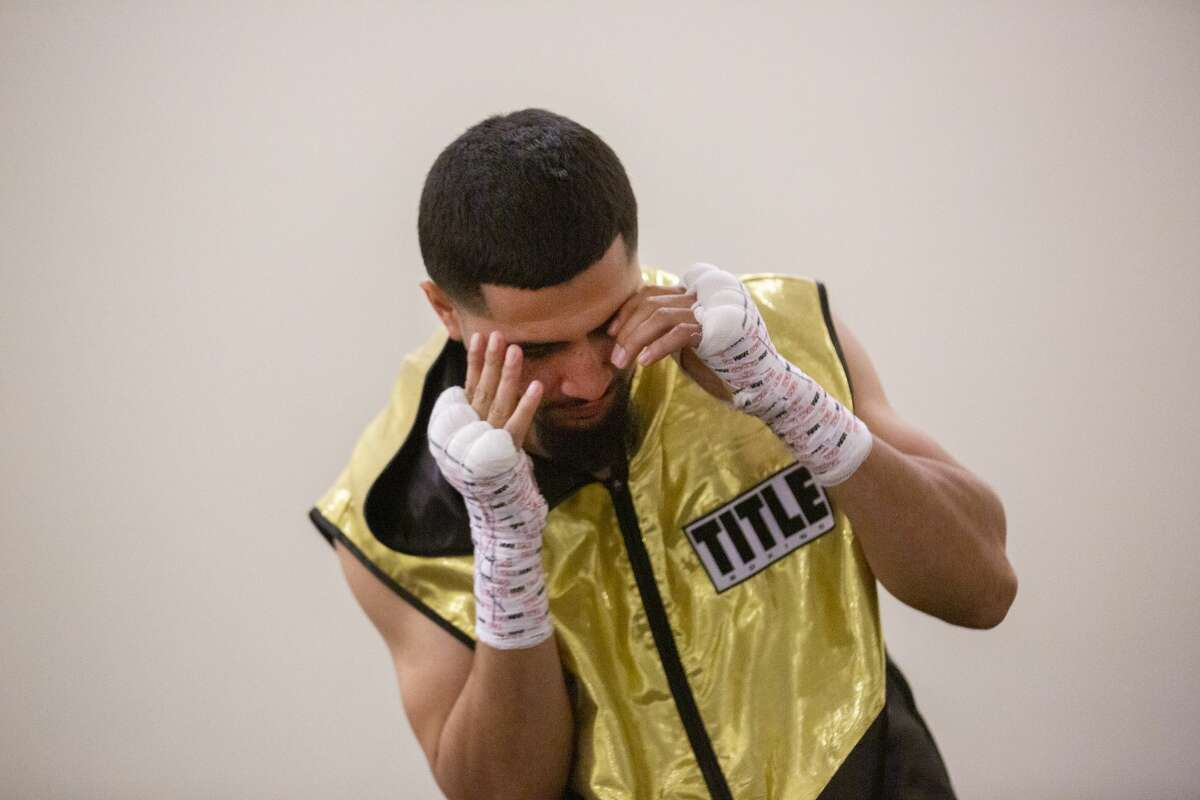 """Joseph Rivera, 22, warms up before his boxing match on Nov. 23, 2019, in Houston. It was a big moment for the young fighter, with one of his idols, Evander """"The Real Deal"""" Holyfield, in attendance. It came after a devastating month in which the boxing gym run by Rivera's father was burgled."""