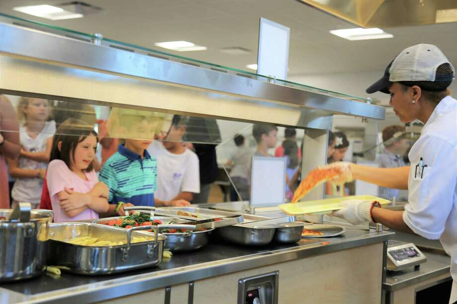 Flik Food Services Worker Yahaira Mendez helps New Canaan Country School students make their hot lunch selections. Photo: Contributed Photo