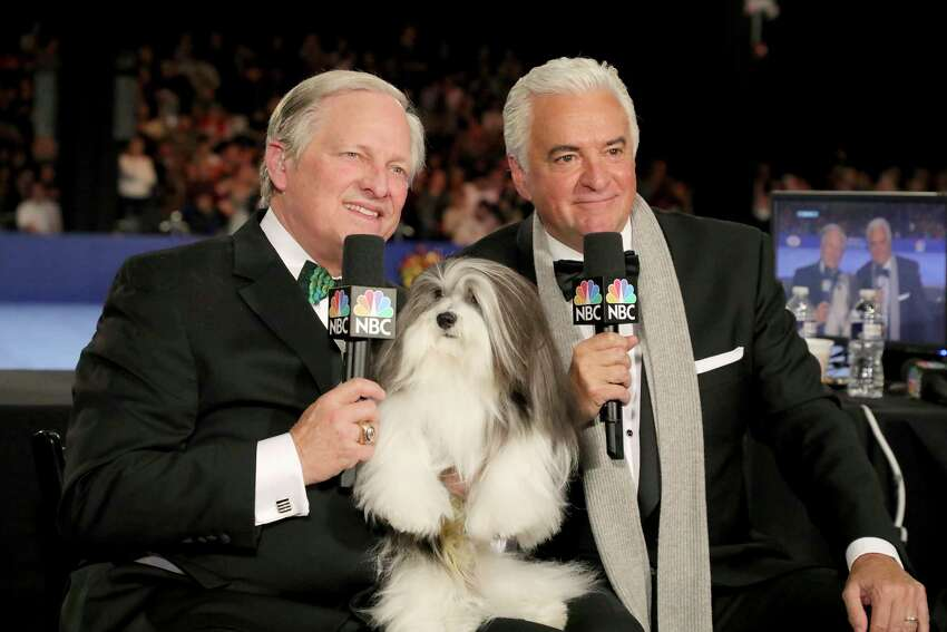This image released by NBC shows David Frei, left, and host John O'Hurley posing with a havanese dog at The National Dog Show in Philadelphia. The annual parade of pooches has become one of the highest-rated shows of Thanksgiving.