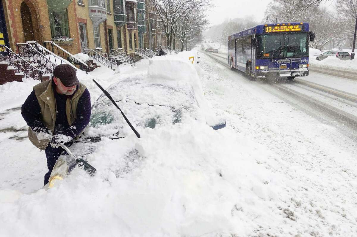 Jack McAvoy of Albany works to clear the snow covering his car on Madison Ave. on Monday, Dec. 2, 2019, in Albany, N.Y. (Paul Buckowski/Times Union)