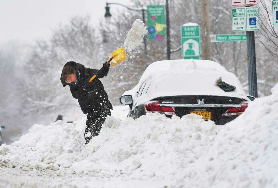 Callie Criswell of Albany works to get her car out of the snow bank created by plows on Madison Ave. on Monday, Dec. 2, 2019, in Albany, N.Y. (Paul Buckowski/Times Union)