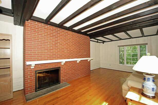 The family room has a fireplace against a wall of red brick, a beamed ceiling, and wood paneled walls.