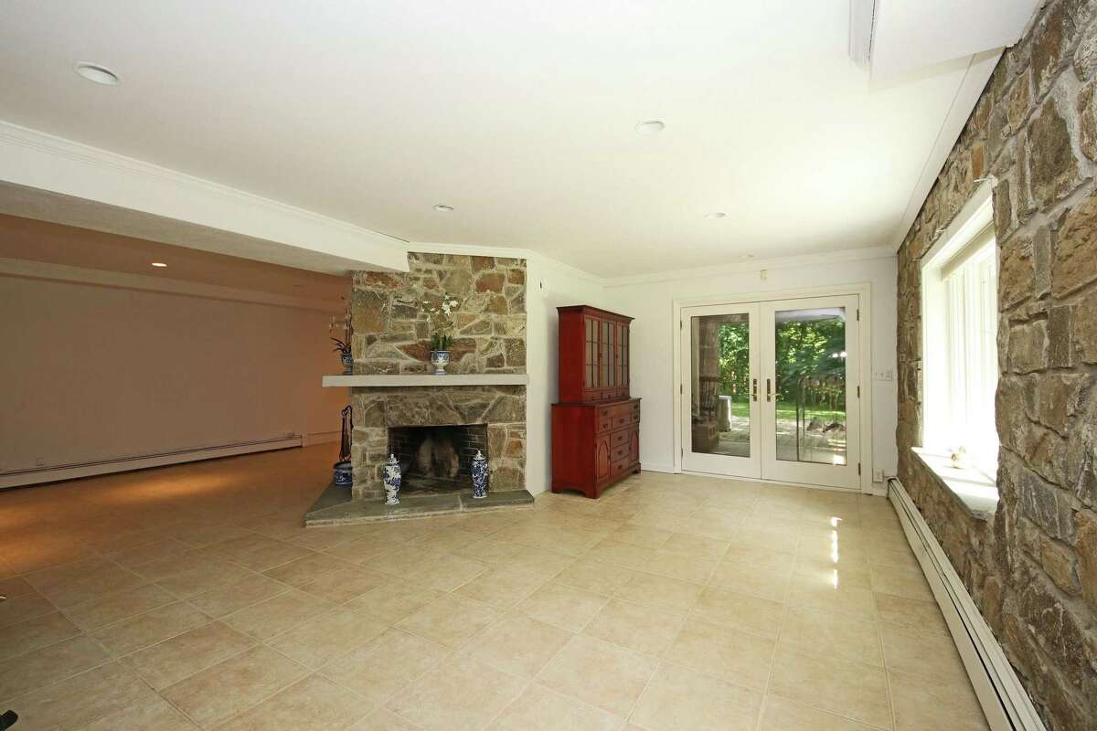 In the walk-out lower level there is a triangular, two-sided stone fireplace and glass French doors to the patio and heated in-ground swimming pool.