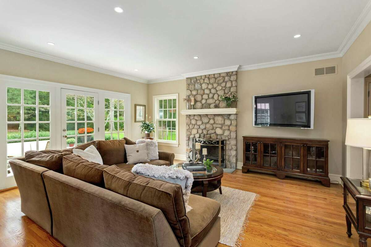 In the family room there is a floor-to-ceiling stone fireplace and a door to the patio.