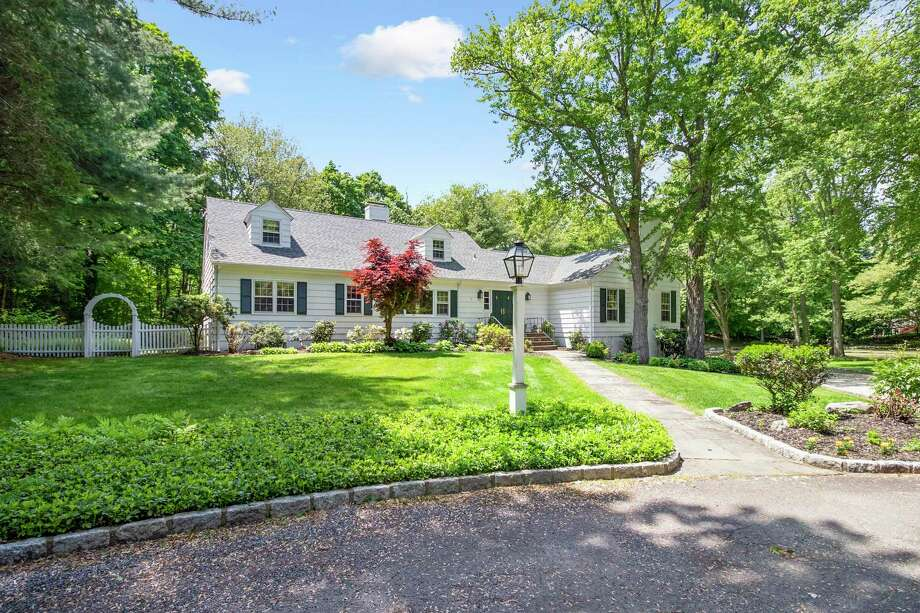 The waterfront Cape Cod-style house at 8 Placid Lake Lane sits on a 1.28-level property with a pond at the end of a private cul-de-sac.
