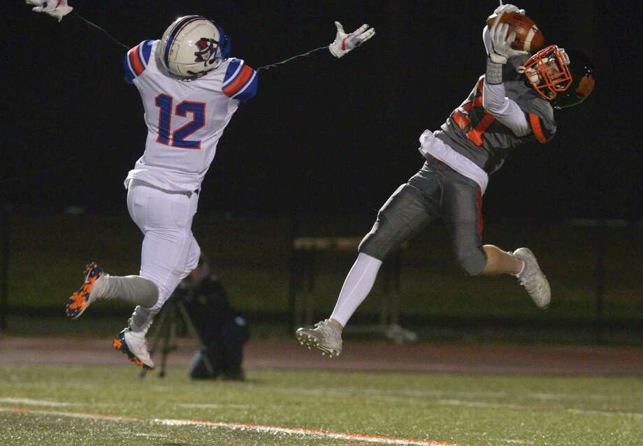 Ridgefield's Owen Gaydos (21) pulls in a pass while being defended by Danbury's Deaven Smith (12) in the football game between Danbury and Ridgefield high schools. Wednesday night, November 27, 2019, at Ridgefield High School, Ridgefield, Conn. Gaydos turned and ran it in for a touchdown. Photo: H John Voorhees III / Hearst Connecticut Media / The News-Times