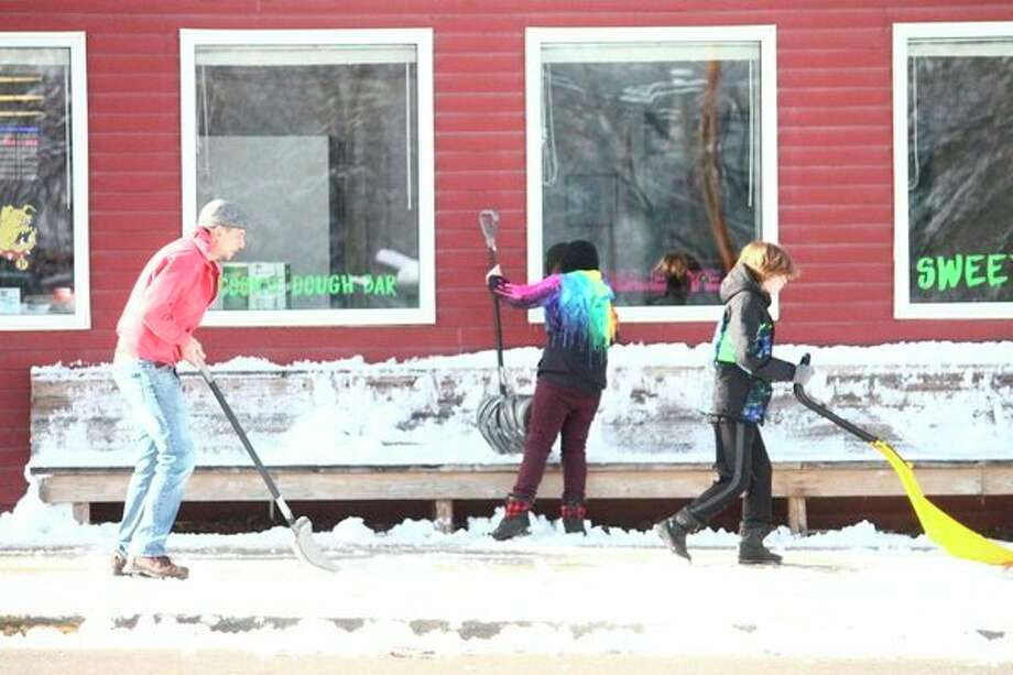 Pictured from left are Bryan Conley, Thatcher Conley and Marcus Shepherd, shoveling snow outside of Toppings Frozen Yogurt, in Big Rapids. Five inches of snow fell in Big Rapids over the weekend. (Pioneer photo/Julie Norwood)