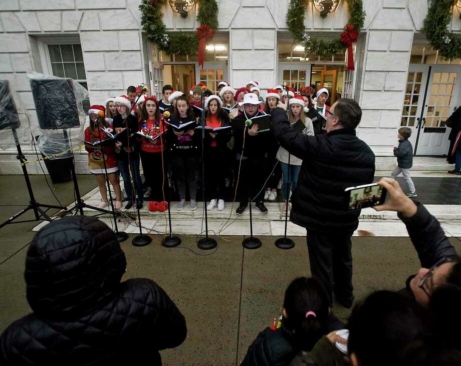 The Greenwich High School Chamber Singers entertain the crowd with Christmas songs at the annual Holiday Tree Lighting ceremony at Town Hall in 2018. The event returns Dec. 6. Photo: Scott Mullin / Hearst Connecticut Media File Photo / The News-Times Freelance