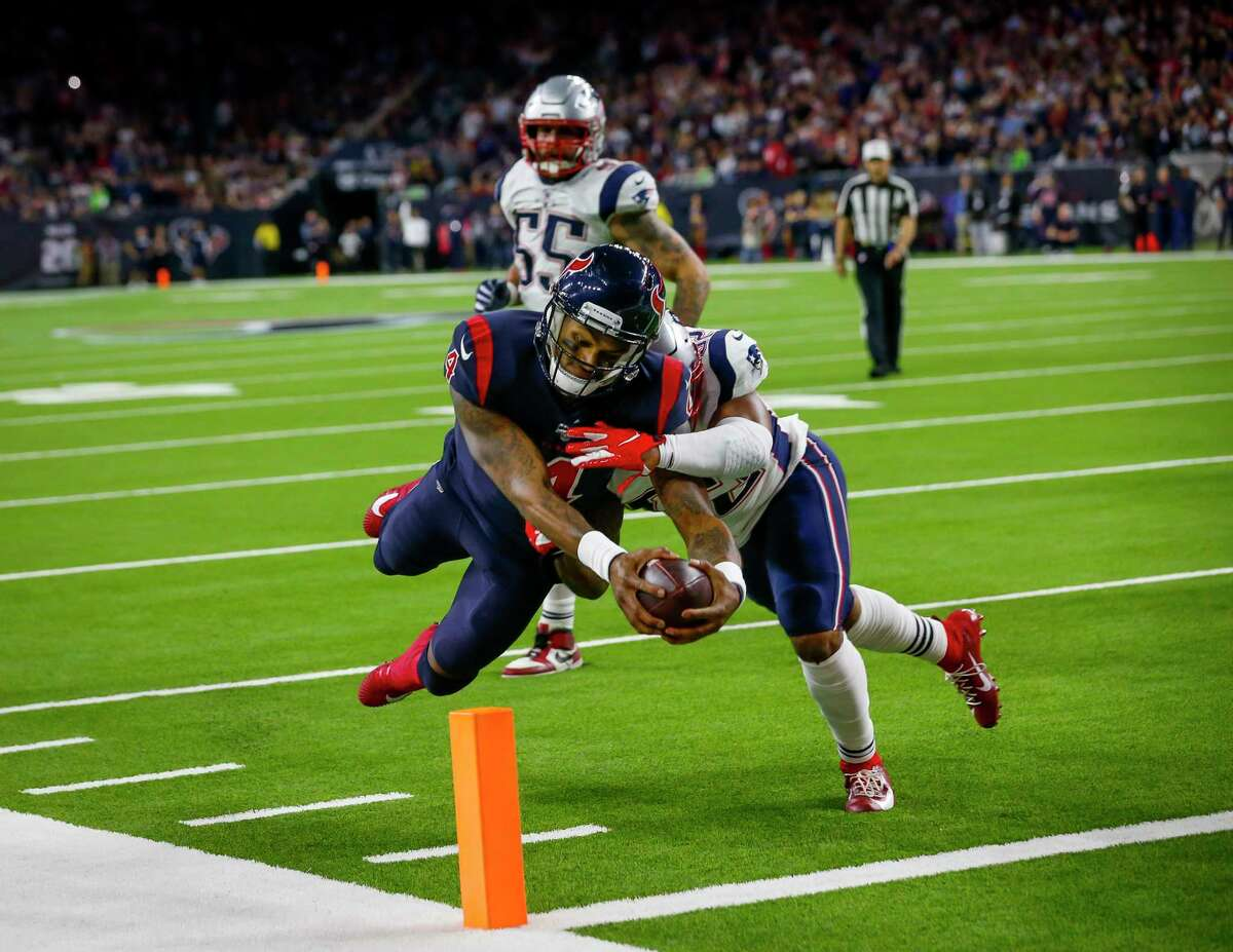 Deshaun Watson dives into the end zone past Patriots linebacker Elandon Roberts after a six-yard touchdown pass from wide receiver DeAndre Hopkins.