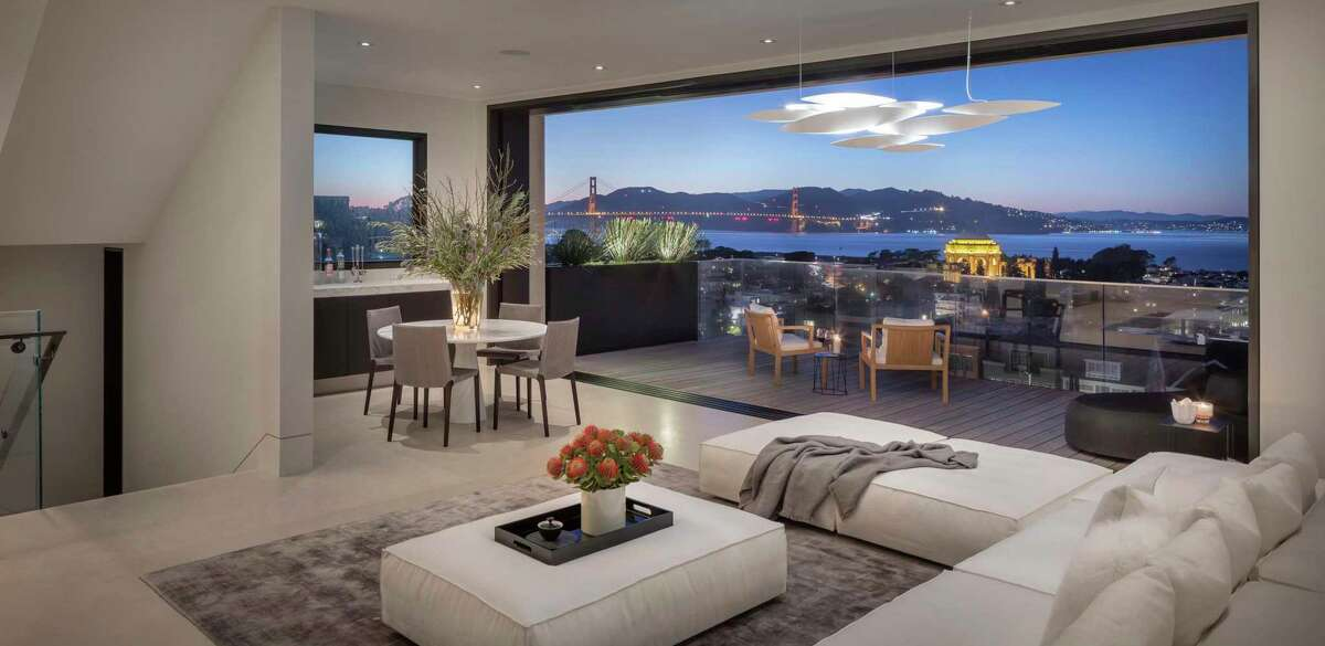 Retractable glass walls in the family room of 2646 Union St. in Cow Hollow open to a view terrace looking out at the Golden Gate Bridge and San Francisco Bay.