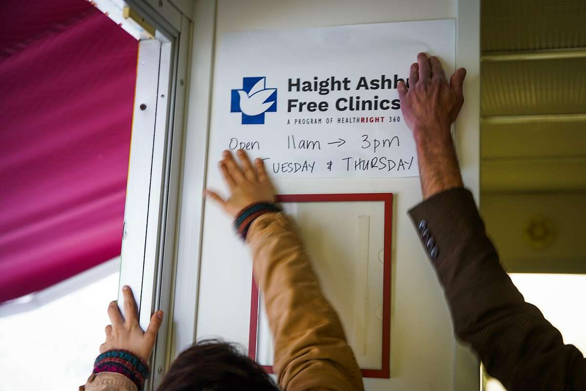 Director of philanthropy Jeff Schindler (right) and public affairs manager Erika Frommer put a sign up on the Health Right 360 mobile services van in San Francisco, California, on Monday, Dec. 2, 2019.