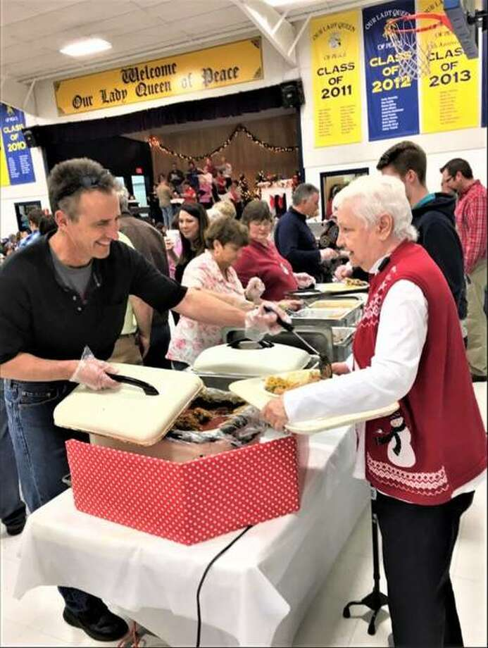 Our Lady Queen of Peace Church parishioner Joe Grabowski serves a guest at a past smorgasbord dinner. This year's event is planned Dec. 8.