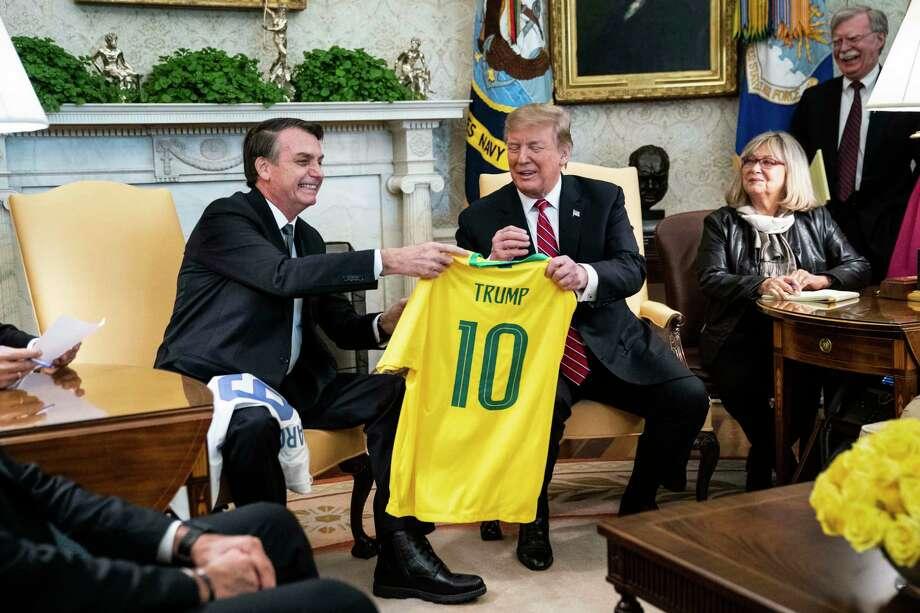 Brazilian President Jair Bolsonaro and President Donald Trump trade soccer jerseys in the Oval Office in March 19. Photo: Washington Post Photo By Jabin Botsford / The Washington Post