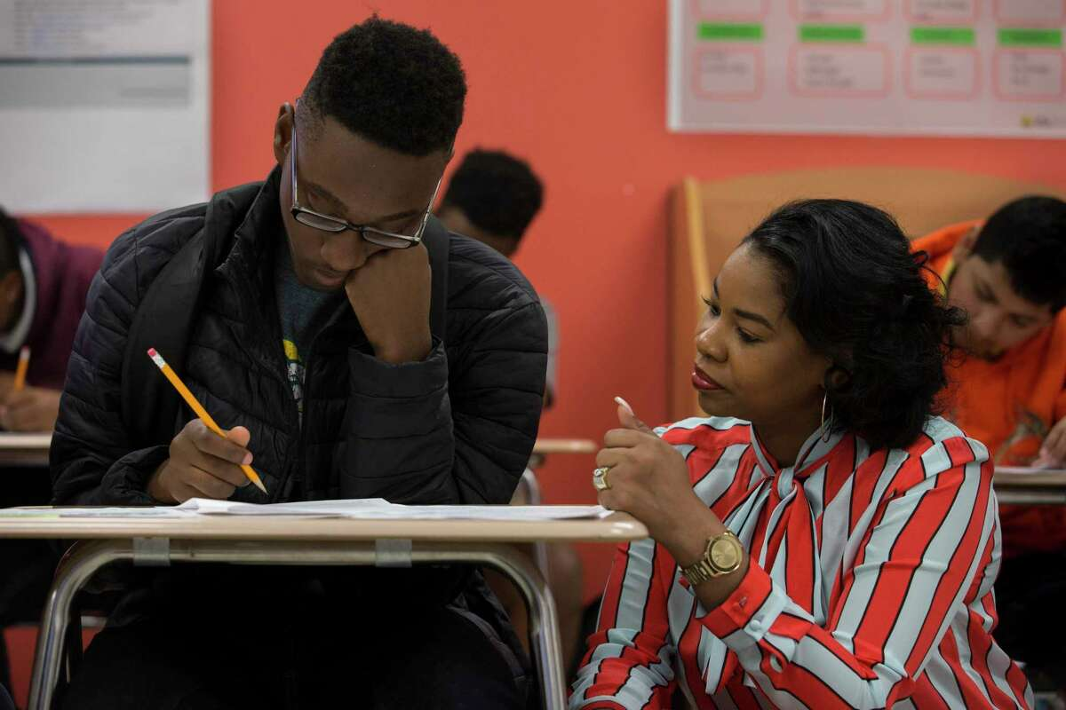 Worthing High School Principal Dr. Khalilah Campbell-Rhone helps student Shemar Galloway with a worksheet during an English class to learn about identity on Tuesday, Oct. 29, 2019, in Houston. Galloway is part of Miles Ahead, a program that identifies high-potential freshmen and sophomore male students at three HISD high school and aims to get them enrolled in the nation's most prestigious universities.