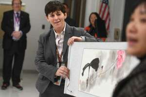 Shelton High Headmaster Beth Smith, left, unfurls a Chinese painting, a gift from Jian Ping High School, Shelton's sister school in Shanghai, China, during a visit by students from the school to Shelton, Conn. on Tuesday, Jan. 29.
