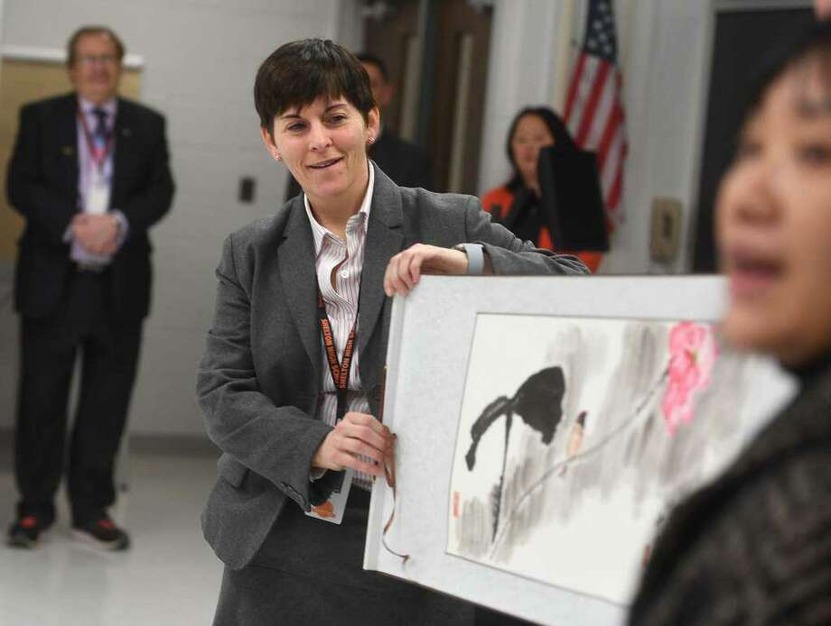 Shelton High Headmaster Beth Smith, left, unfurls a Chinese painting, a gift from Jian Ping High School, Shelton's sister school in Shanghai, China, during a visit by students from the school to Shelton, Conn. on Tuesday, Jan. 29. Photo: Brian A. Pounds / Hearst Connecticut Media / Connecticut Post