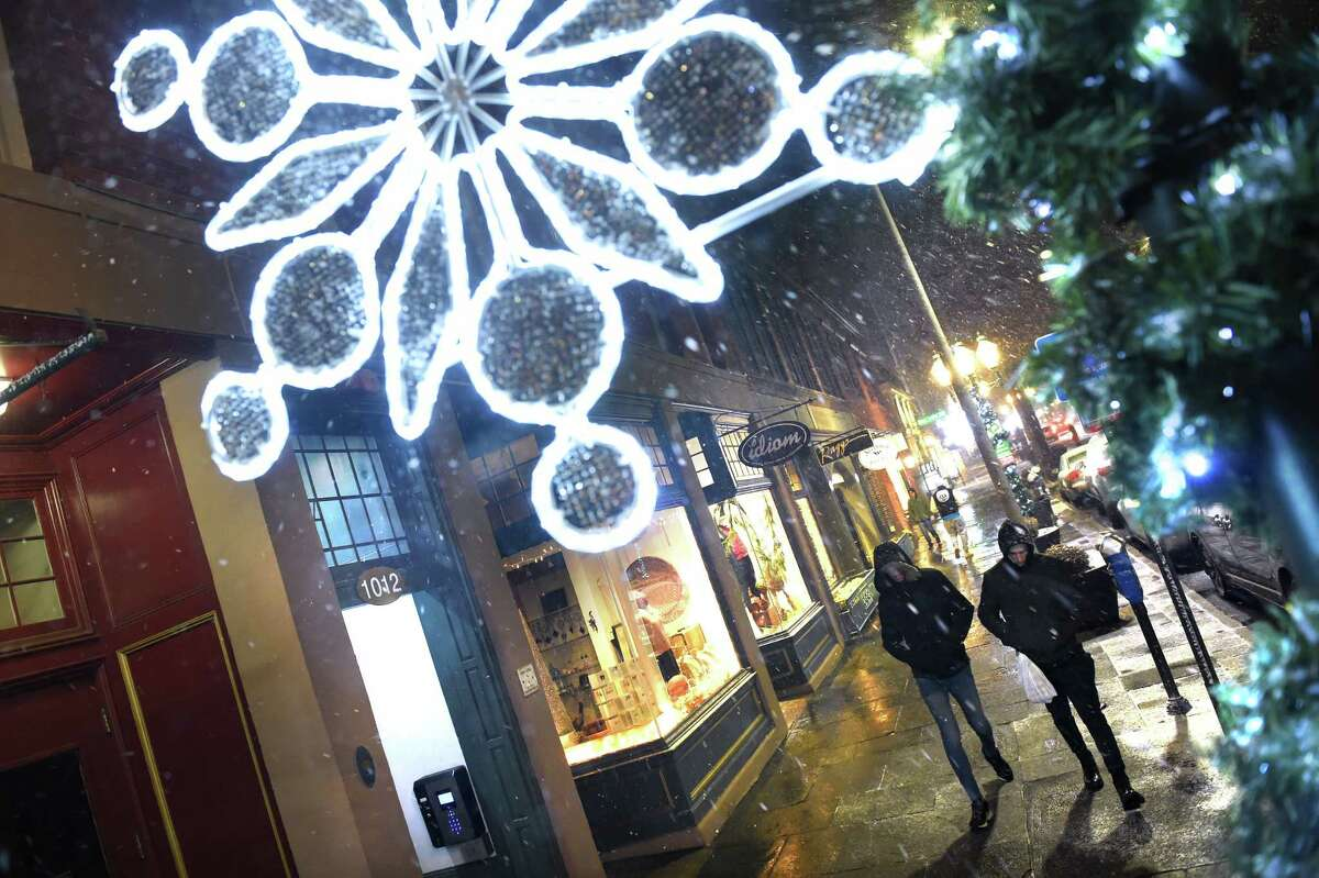 Snow begins to fall in New Haven as people walk along Chapel Street on December 2, 2019.