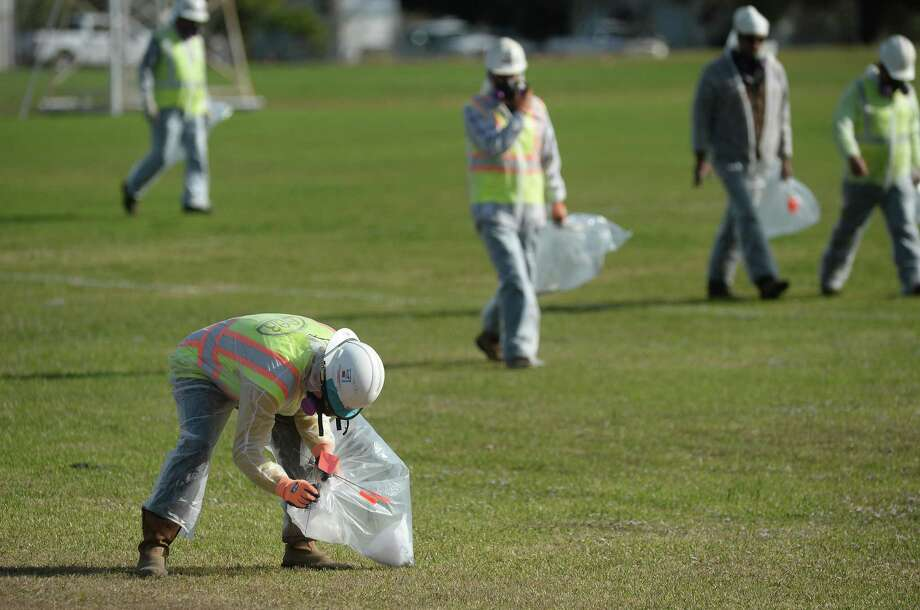 Work crews comb through areas surrounding Port Neches - Groves High School Monday, marking suspected debris with flags. The debris was later collected by haz-mat crews. Photo taken Monday, December 2, 2019 Kim Brent/The Enterprise Photo: Kim Brent / The Enterprise / BEN