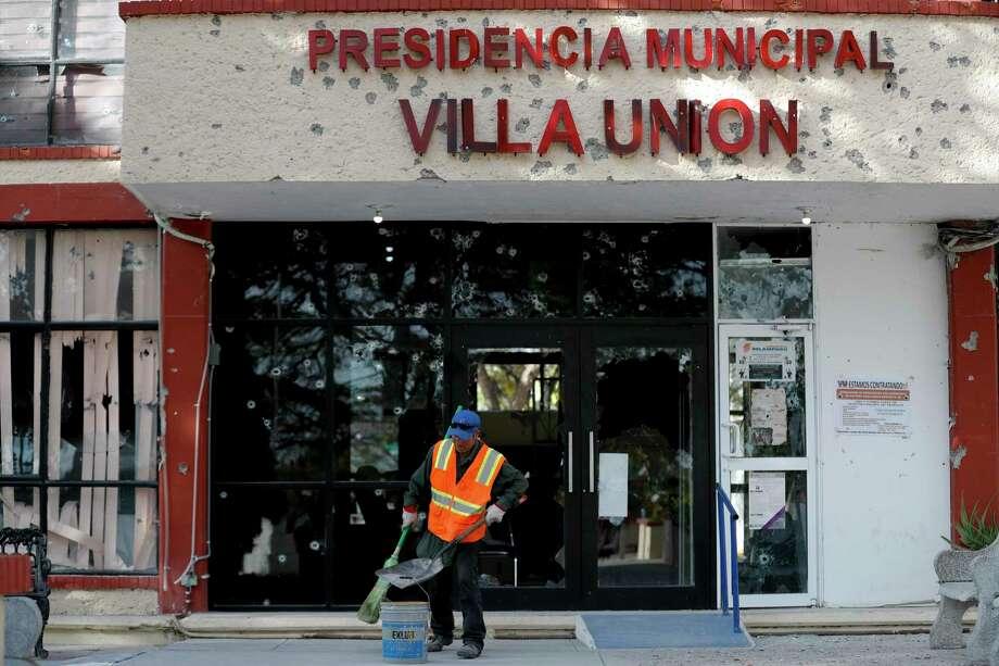 Un trabajador limpia la calle frente al ayuntamiento del pueblo de Villa Unión, México, tras un tiroteo que lo dejó lleno de agujeros de bala, el lunes 2 de diciembre del 2019. Photo: Eduardo Verdugo /Associated Press / Copyright 2019 The Associated Press. All rights reserved