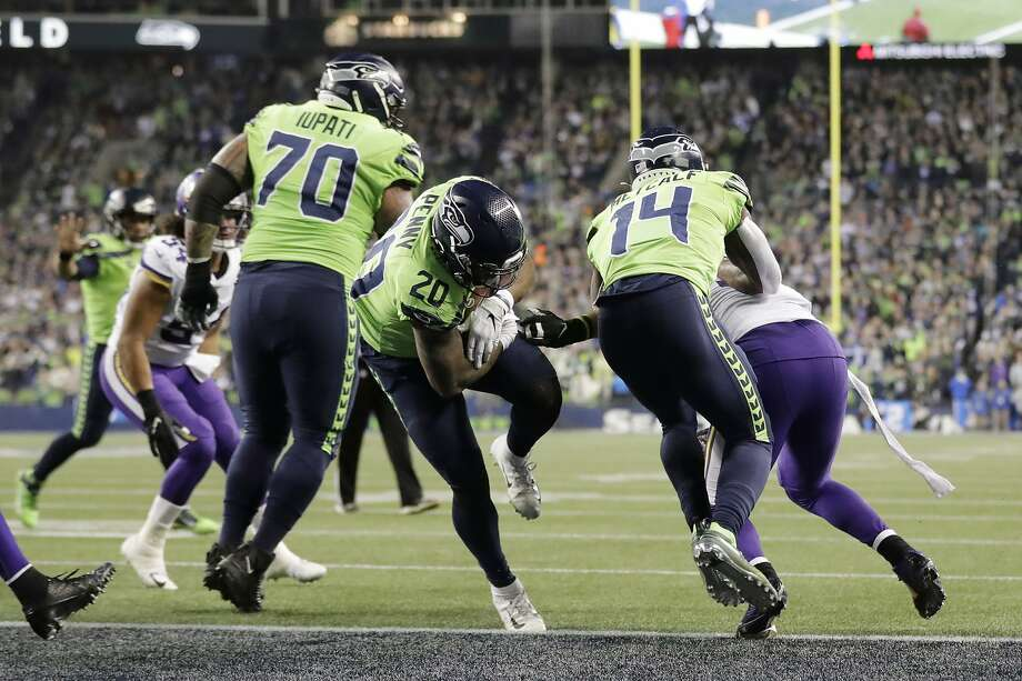 Seattle's Rashaad Penny (20) scores a touchdown on a 1-yard run. He also scored a touchdown on a pass reception. Photo: Ted S. Warren / Associated Press