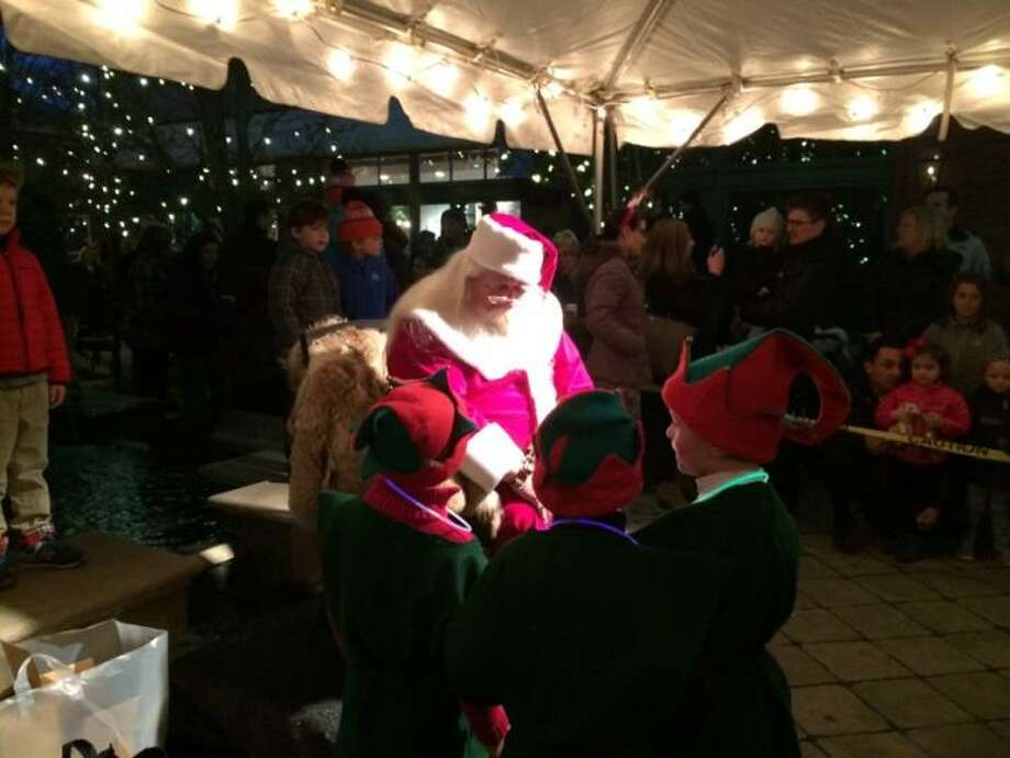 Holiday Magic, along with Santa, seen here giving instructions to elves last year, returns to Grove Street Plaza this Saturday - festivities begin at 4 p.m. Photo: Darien Chamber