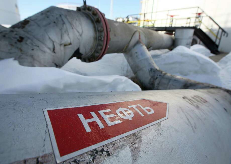 A flow direction arrow reading 'Oil' sits on an oil pipe at a pumping station, operated by Rosneft, in the Samotlor oilfield near Nizhnevartovsk, Russia, on March 20, 2017. Photo: Bloomberg Photo By Andrew Rudakov. / © 2017 Bloomberg Finance LP