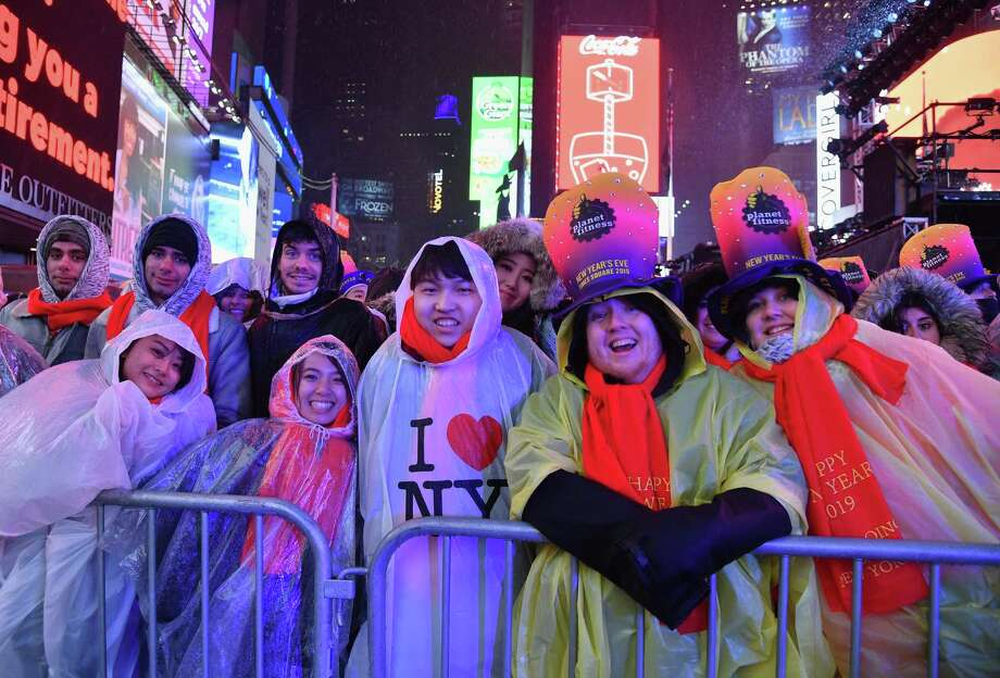 Revelers smile under the rain as people gather for the New Year's Eve celebration Dec. 31, 2018, in Times Square in New York. Photo: Getty Images / AFP or licensors