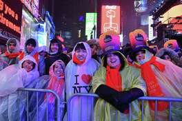 Revelers smile under the rain as people gather for the New Year's Eve celebration Dec. 31, 2018, in Times Square in New York.
