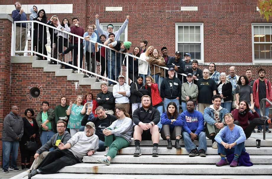 Wesleyan University student and community volunteers who organized a celebration to mark 80 years of the school's radio station WESU-FM 88.1 gathered for a photograph outside the Public Affairs Center in Middletown in November. Photo: Tom Dziman Photo
