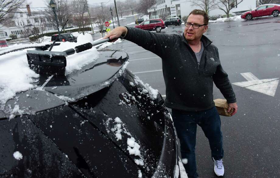 Rich Connington cleans snow off his car after shopping at Wilton Market during the forecasted Nor'Easter Wednesday, March 21, 2018, in Wilton, Conn. There was barely two inches of snow by 5pm. Photo: Erik Trautmann / Hearst Connecticut Media / Norwalk Hour