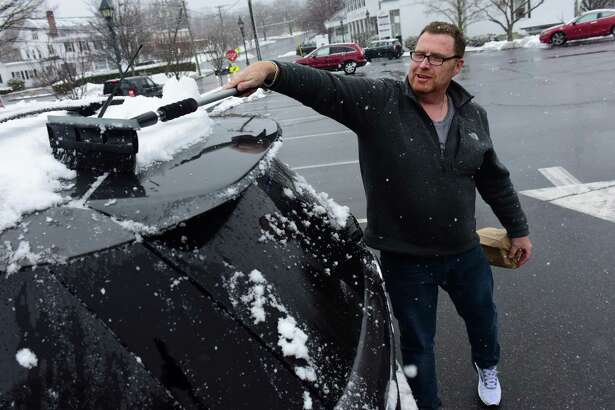 Rich Connington cleans snow off his car after shopping at Wilton Market during the forecasted Nor'Easter Wednesday, March 21, 2018, in Wilton, Conn. There was barely two inches of snow by 5pm.