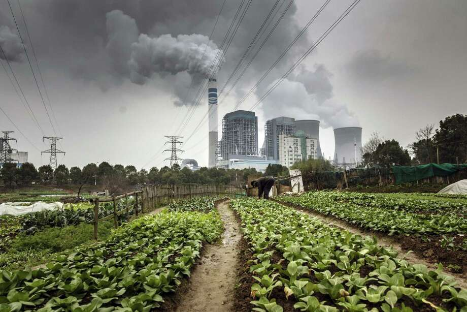 A man tends to vegetables growing in a field as emissions rise from cooling towers at a coal-fired power station in Tongling, Anhui province, China, on Jan. 16, 2019. Photo: Bloomberg Photo By Qilai Shen / © 2019 Bloomberg Finance LP