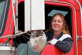 Woman truck driver looking out of a semi-truck while driving.