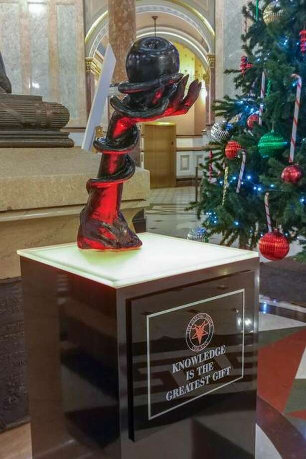 Seasonal decorations are filling the Illinois Capitol rotunda, including a satanic sculpture near a traditional Christmas tree. The winter displays, installed for 30 days, are protected by the First Amendment of the U.S. Constitution, so long as the displays are not paid for by taxpayer dollars.