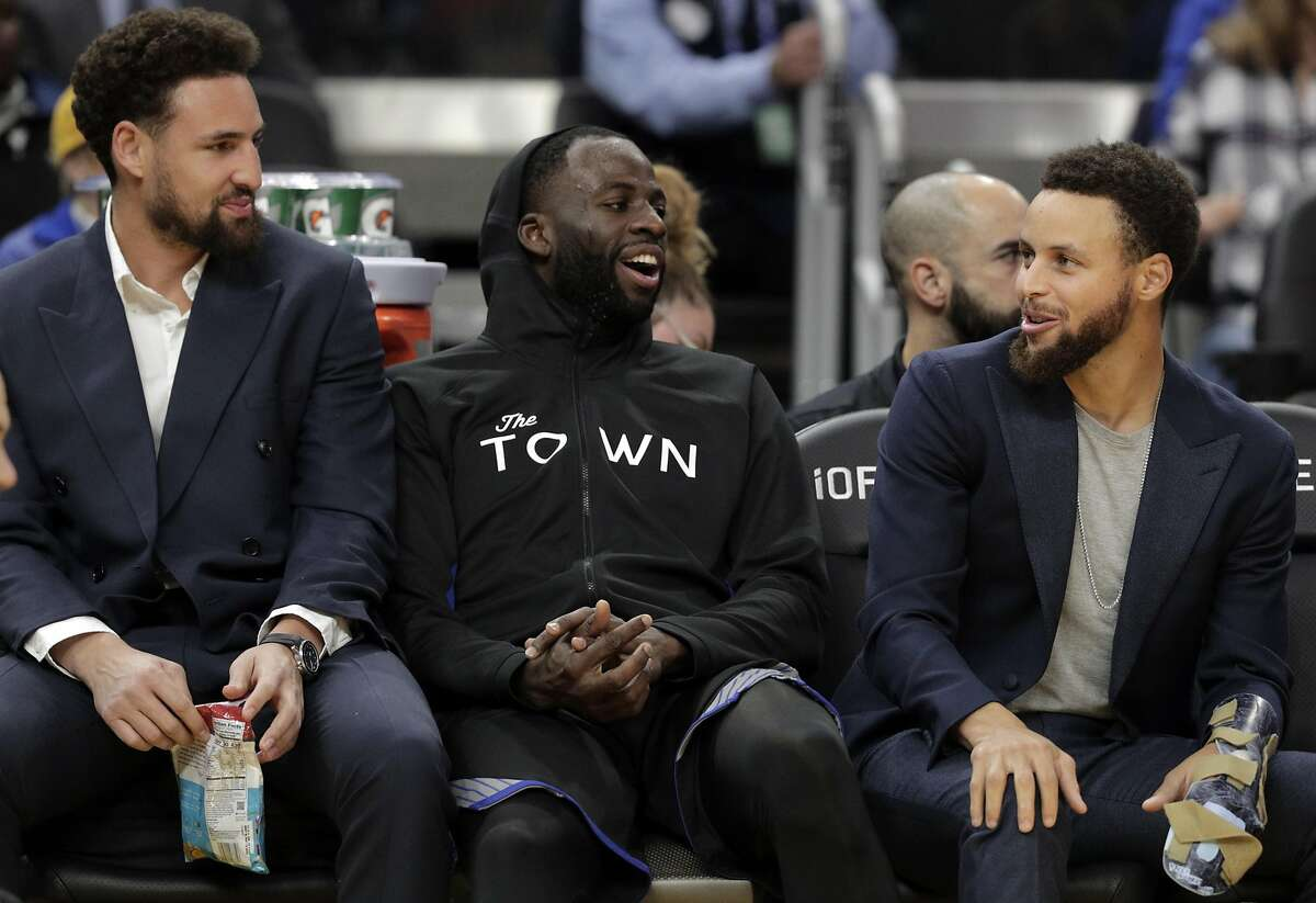 Stephen Curry (30), Draymond Green (23) and Klay Thompson (11) on the bence in the first half as the Golden State Warriors played the Chicago Bulls at Chase Center in San Francisco, Calif., on Wednesday, November 27, 2019.