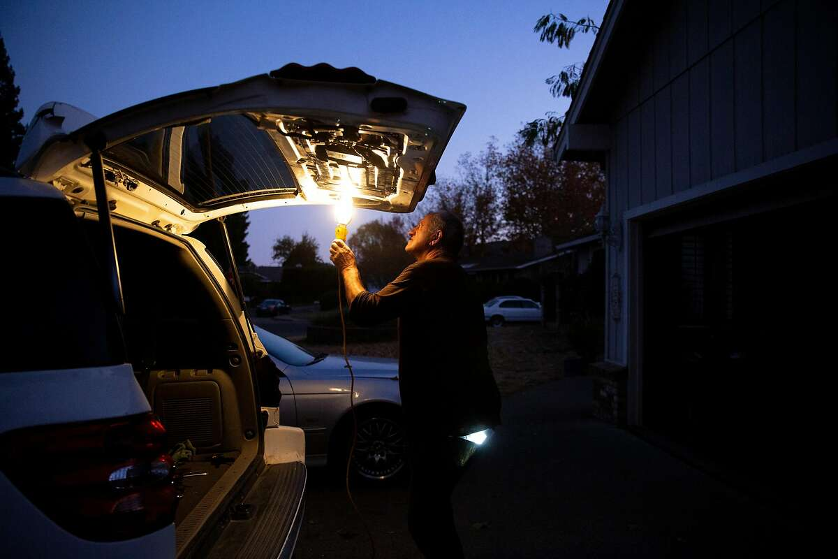 William Douglas Hitt outside his home fixes his power window before driving to his upholstery class on Wednesday, Nov. 20, 2019, in St. Helena, Calif. The power is out at his neighborhood off of Spring Street. Hitt is using a generator to power his light. PG&E has shut off the power to more than 40,000 homes in an effort to prevent wildland fires.