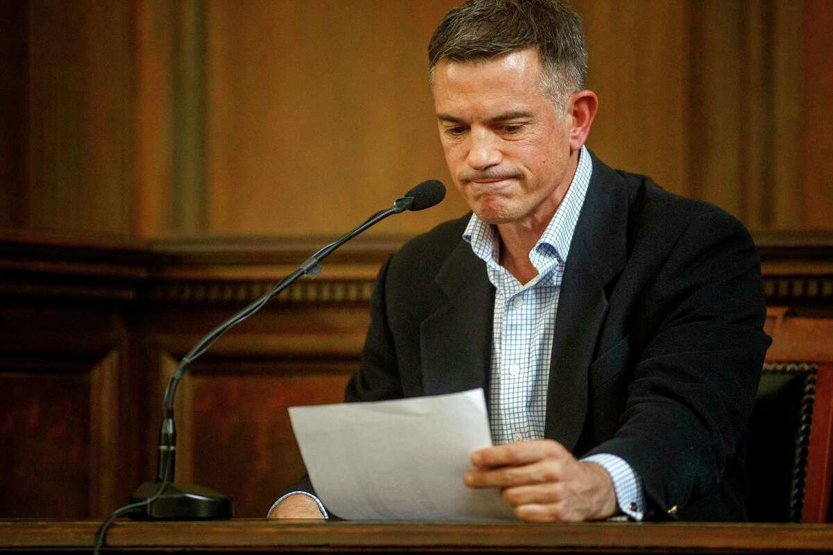 Fotis Dulos examines a financial statement during his testimony in a civil case Tuesday in Hartford.