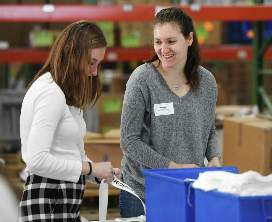 Henkel volunteers Caitlin Fahey, left, and Becky Zaguli help out at the Giving Tuesday emergency kit assembly line at the Americares Headquarters in Stamford, Conn. Tuesday, Dec. 3, 2019. Americares staff worked with volunteers from Stamford-based consumer goods company Henkel to assemble 3,000 emergency kits for disaster survivors in celebration of Giving Tuesday. Each kit contains essential hygiene items that will be stored at the Americares global distribution center and eventually distributed to families displaced by tornadoes, hurricanes, flooding, wildfires and other emergencies worldwide. Photo: Tyler Sizemore / Hearst Connecticut Media / Greenwich Time