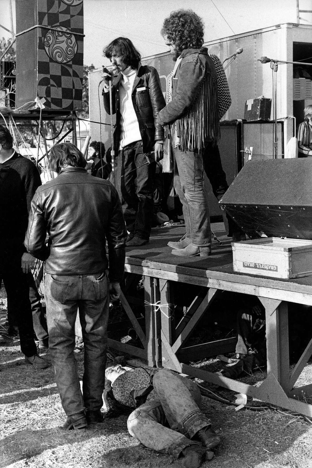 A girl lies in front of the stage as The Rolling Stones tour manager Sam Cutler tries to placate the crowd at The Altamont Speedway on December 6, 1969 in Tracy. Next to him is Michael Lang, one of the promoters of Woodstock earlier that year.