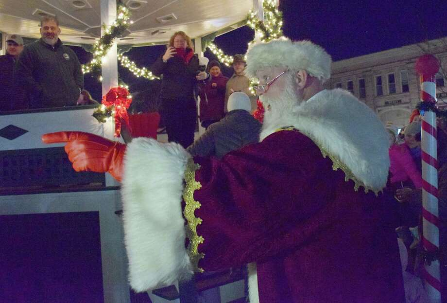 Spectrum/The Greater New Milford Chamber of Commerce held the annual lighting of the trees on the Village Green Nov. 30, 2019. Santa Claus made an appearance and visited with attendees after the trees were lighted. This is the 53rd year the trees have been put up by the Men's Club of the New Milford United Methodist Church and lighted. Above, Santa acknowledges a believer in the crowd of those gathered for the lighting of the trees. Photo: Deborah Rose / Hearst Connecticut Media / The News-Times  / Spectrum