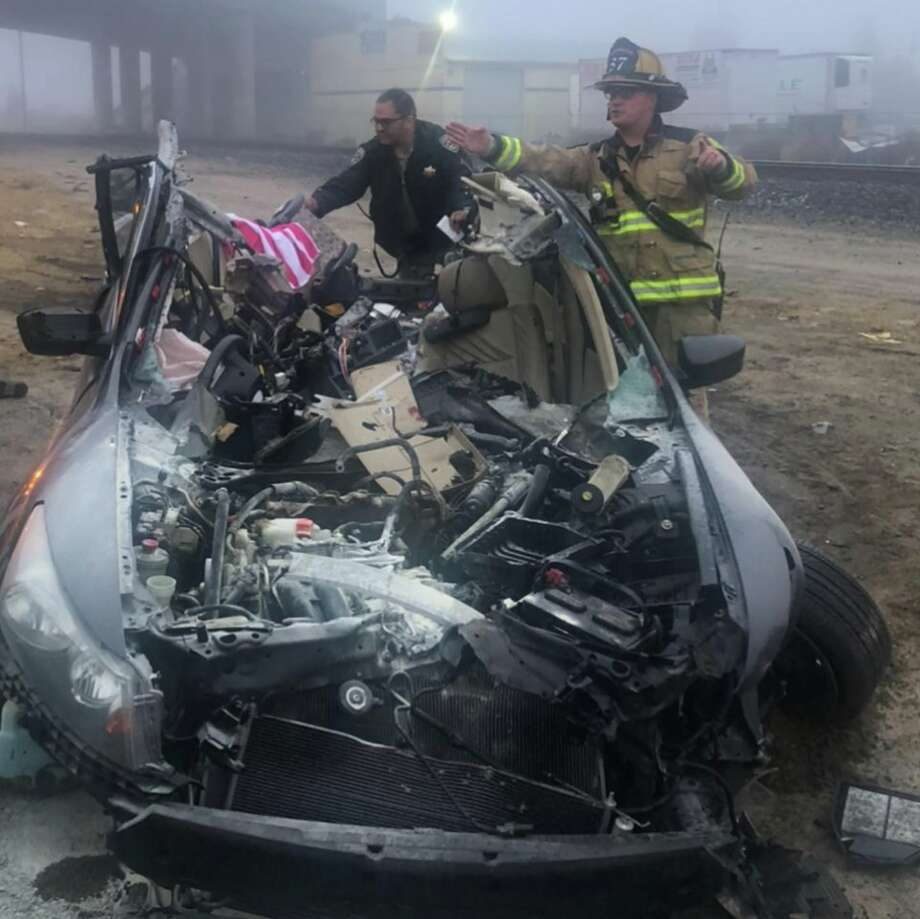 California Highway Patrol officers inspect the wreckage of a car that rammed into a big rig in Fresno. Amazingly, the driver was able to walk out of  the car. Photo: CHP Fresno