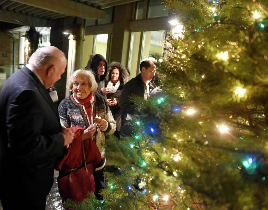 Old Greenwich's Helen Delago chats with Greenwich Hospital President and CEO Norman G. Roth beside the just-lit evergreen tree at the Tree of Light Celebration at Greenwich Hospital in Greenwich, Conn. Monday, Dec. 2, 2019. Presented by the hospital's Palliative Care Program, the non-denominational community tree lighting celebrated the lives of loved ones lost. The annual event featured readings from hospital staff and clergy, music from the Grace Notes, a candlelight procession and tree lighting. Photo: Tyler Sizemore / Hearst Connecticut Media / Greenwich Time